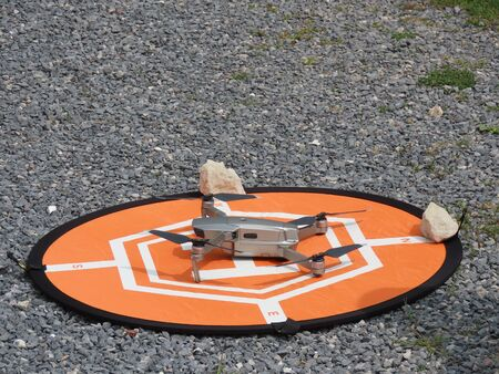 Small hobby class drone quadcopter on orange landing pad, just landed or ready to take off, grey pebbles in background as copy space
