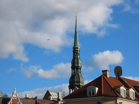 Tower of St Peter church in Riga, Latvia, view over rooftops in old town on a sunny summer day