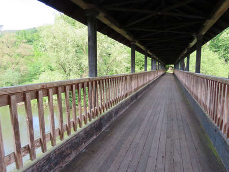 Wooden pedestrian bridge with roof crossing Sauer river in Weilerbach on border of Luxembourg and Germany on sunny summer day