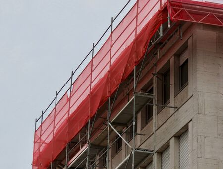 Scaffoldings covered with red safety nets around and on top of a multistory house during repairs. Cloudy summer day Archivio Fotografico