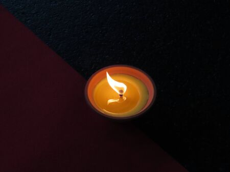 Mosquito repellent outdoor candle with flame on a dark background part of which is red carpet  Stock Photo