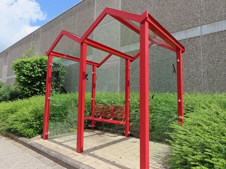 Bus stop in Walferdange, Luxembourg: red metal frame and seats, transparent glass walls, green shrubs and grey wall of a shop behind it