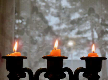 Three burning candles almost spent, in old ceramics candleholder, against blurred out background of grey winter day