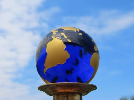 Blue planet Earth on the background of blue sky with white clouds: Blue glass ball with printed map of golden continents, seen South America and Atlantic Ocean