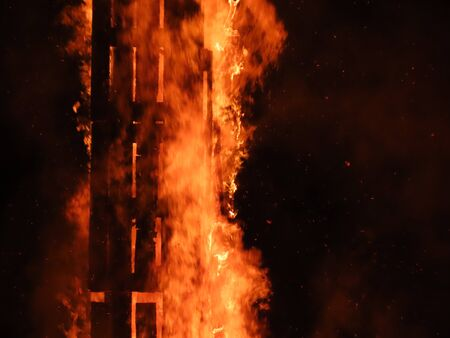 Big bonfire at night with log column as basic structure, close up, flames with motion blur Stock Photo