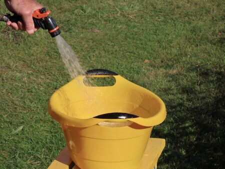 Man filling a yellow washbasin using water hose outside on a sunny summer day 版權商用圖片