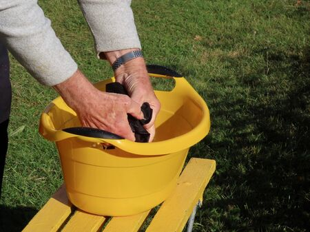 Man washing by hand black clothes in a yellow washbasin outside on a sunny summer day