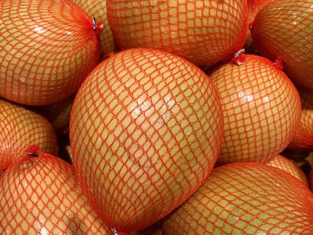 Grapefruits packed in red mesh in shop Stock fotó