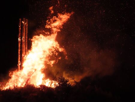 Big bonfire at night with log column as basic structure, flames with motion blur