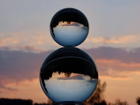 Two crystal balls stacked on one another, evening sky after sunset and dark tree silhouettes showing through Standard-Bild