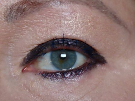 Dark teal coloured eye of an old lady, with carefree violet shadows, blue mascara, and golden highlights, close up
