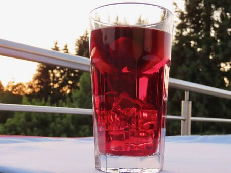 Cold sangria - close up of big glass with ice, cherries, apple slices in summer heat. Blurry background of sunset over dark fir trees, on terrace on park side, white table cloth, metal railings Foto de archivo