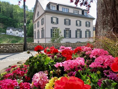 Historic house in Clervaux seen over a flower bed of red geraniums, Luxembourg