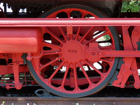 Bright red wheel of parked steam train, well maintained, close up Stockfoto