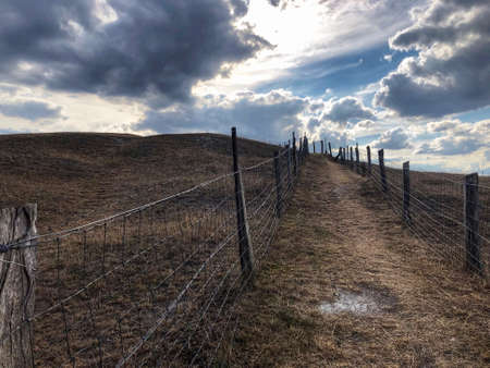 Fenced in path uphill amid brown dried out fields in late summer drought, blue sky and white clouds Banque d'images