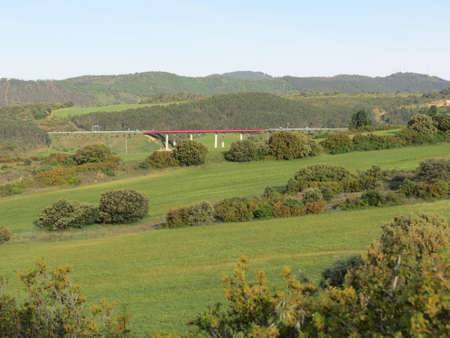 Panoramic Navarra, Spain, landscape with green meadows and modern red bridge in the distance