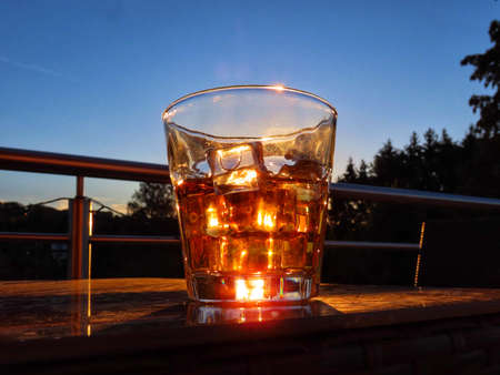 Whiskey with ice close up with red sunset shining through, sky and dark fir trees in background