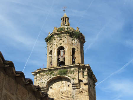 Green plants growing on bell tower of Church of the Crucifix in Puente la Reina, Spain, along Camino de Santiago, bright summer day