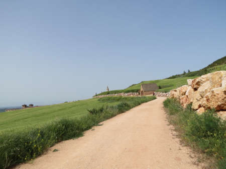 Dirt road approaching Villamayor de Monjardin in Navarra, Spain , stone wall and green fields on the sides, little house seen in distance is medieval water well