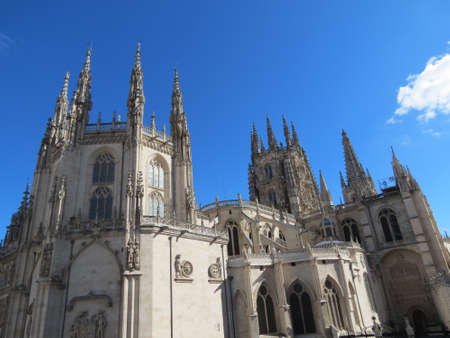Burgos Cathedral in Castile, Spain - big grey gothic church with many towers in sunny summer day.