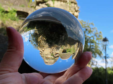 Archeological crypt castle ruins in Luxembourg Grund, through crystal ball with blurry background, on a sunny summer day