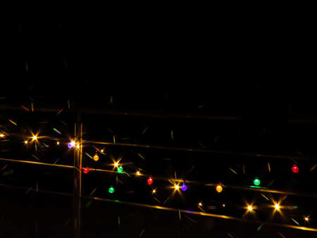 Colourful outdoor lights on a balcony railing on a dark night at Christmas. Star filter used