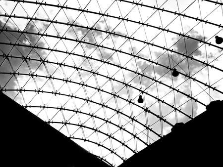 Modern glass roof with filigree grid and clouds. Photo in contrasting black and white