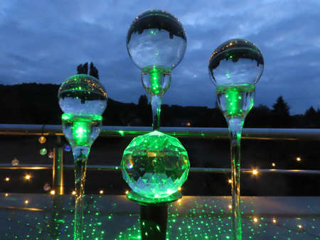 Bright green scattered light reflecting in different crystal balls on a dark sky background Banque d'images