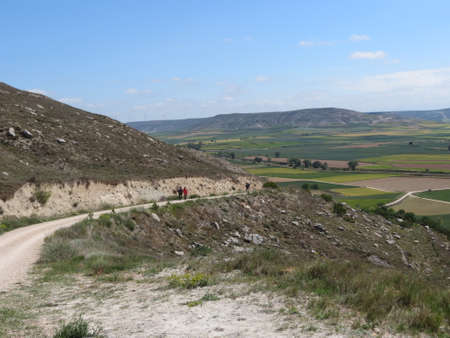 Meseta landscape around Castrojeriz, Spain: pilgrims road leads to unexpected hill in other-ways flat terrain, sunny summer day