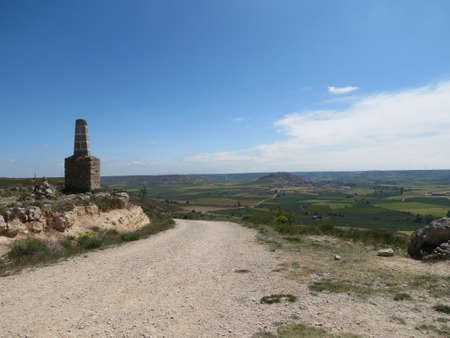 Meseta landscape around Castrojeriz, Spain: pilgrims road leads to unexpected hill in other-ways flat terrain, old road marker tower on the left. Sunny summer day