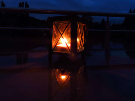 Lantern with burning tea candle in dark night on reflective surface. Long exposure