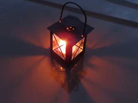 Lantern with burning tea candle in dark night on reflective surface. Top view Banque d'images