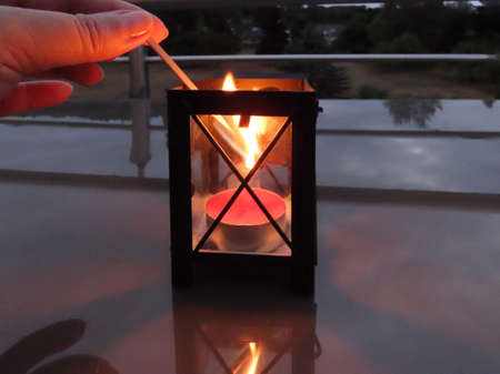 Tea candle being lit with long matchstick inside a traditional small lantern. In dark night on reflective surface