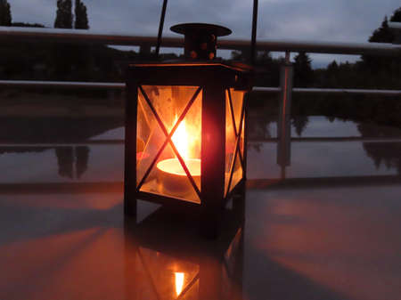 Lantern with burning tea candle in dark night on reflective surface Banque d'images