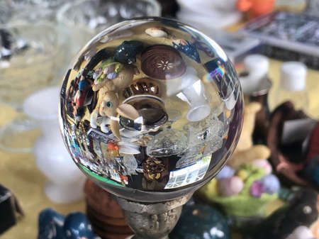 Bokeh image of a flea market seen through crystal ball with blurry background