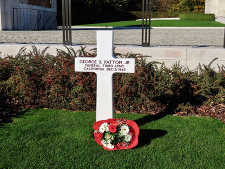 White cross for General George S. Patton Jr., General 3rd army, California, Dec. 21, 1945 with red flowers in American military cemetery in Sandweiler, Luxembourg, October 31, 2020