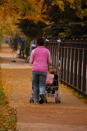A mother wheels her child in a stroller down the sidewalk under a canopy of autumn leaves. Stock fotó