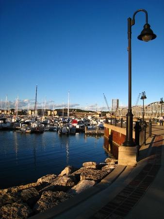 lamp post: Una passerella di curva con una graziosa lampada post gonne un porto turistico pieno di barche su un pomeriggio di fine estate.