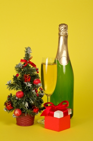 Champagne, small fir-tree in a pot with toys and gifts on a yellow background photo