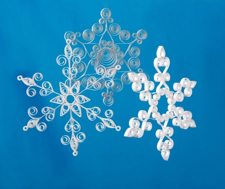 Hand made. Three paper Christmas snowflakes. On blue background photo