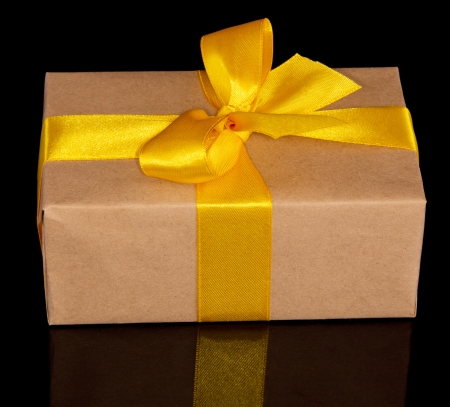 Gift box from rraft paper with a yellow bow isolated on the black photo