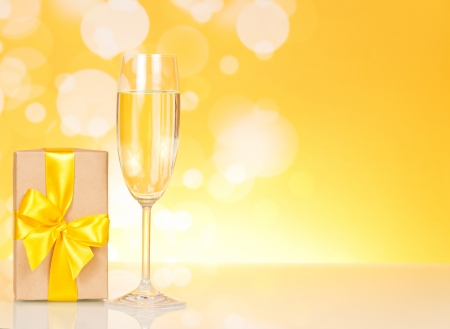 Glass of champagne and gift on an abstract yellow background photo