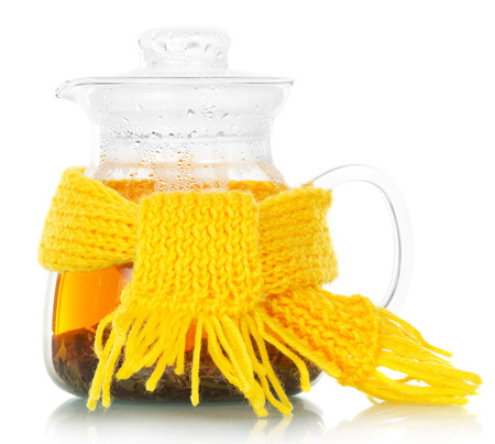 Teapot with tea tied with a yellow scarf on the white Stock Photo