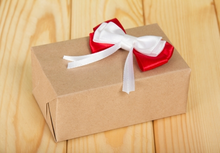 Box from a brown paper with a red-white bow on a wooden surface photo