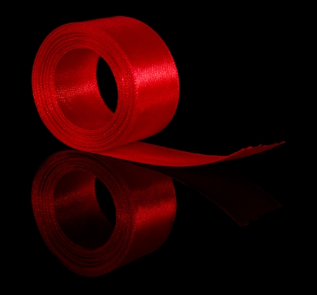hank: Hank of a red satin ribbon isolated on the black