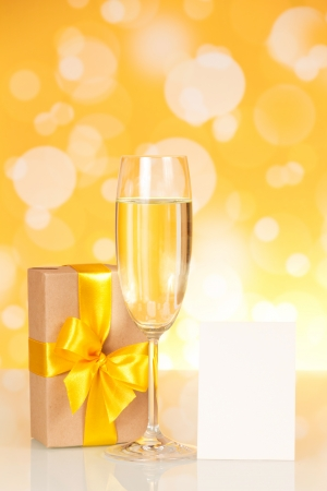 Glass with champagne, a gift and an empty card on an abstract yellow background photo
