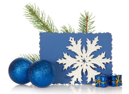 The fir-tree branch, two Christmas toys, small gift boxes, snowflake and the empty card isolated on white photo