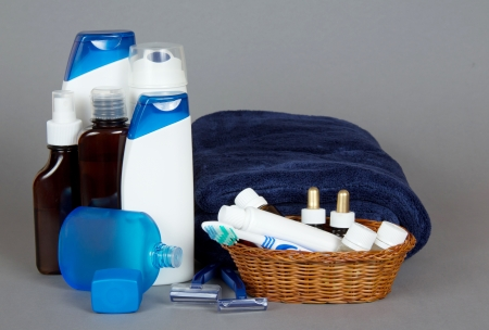 Set for shaving, shampoo, shower gel and a bathing towel on a gray background photo