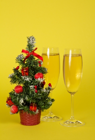 Small Christmas fir-tree in a pot, and two wine glasses with champagne on a yellow background photo