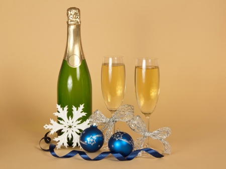 Bottle of champagne, and wine glasses with a silver ribbon, Christmas toys, a snowflake and a serpentine on a beige background photo